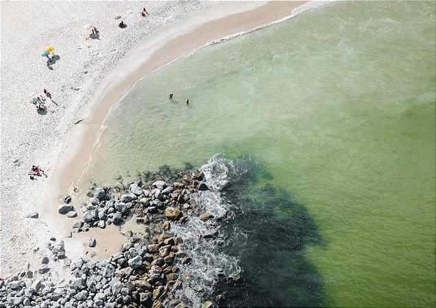 Fotografia aérea de um belo mar esmeralda pedras faixa de areia e banhistas
