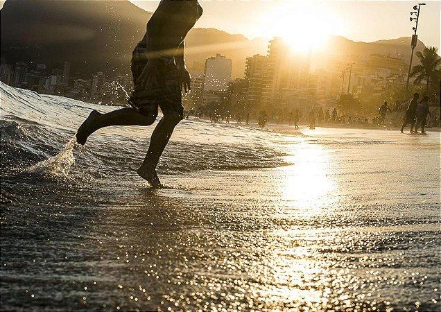 Banhista saindo do mar em fim de tarde dourado com contexto urbano