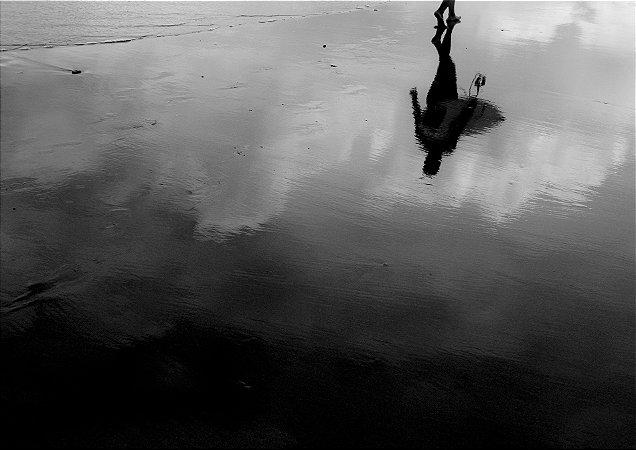 Reflexo de surfista com sua prancha na areia