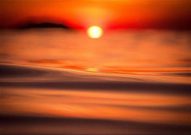 Nascer do sol com forte reflexo laranja no mar