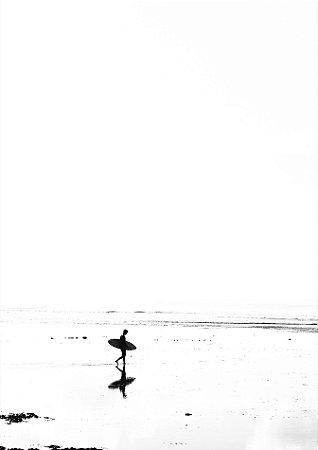 Surfista com sua prancha andando na praia em preto e branco