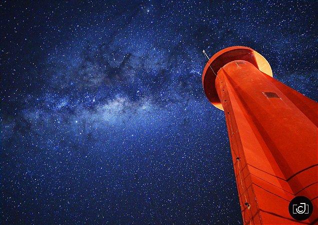 Farol contrastando com céu estrelado