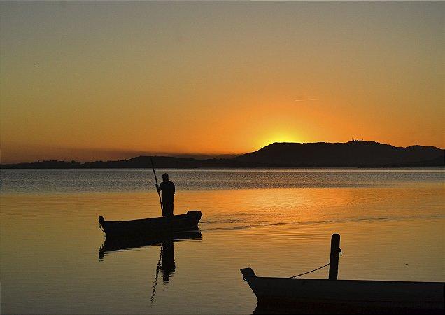 Homem em jangada aproveitando um belo pôr do sol