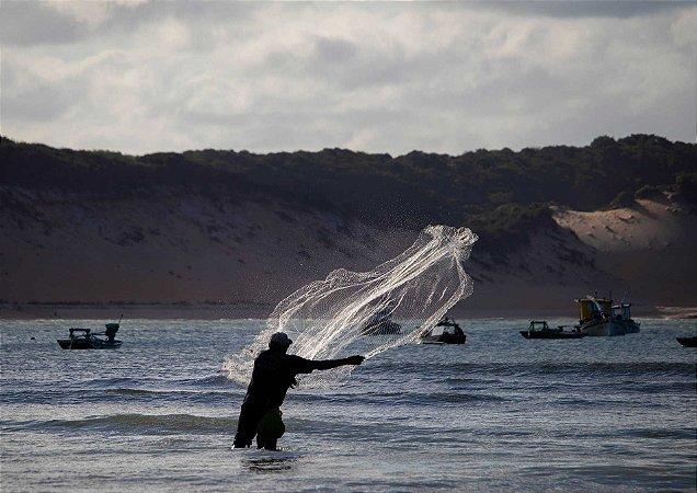 Pescador lançando sua rede à sorte em Baía Formosa