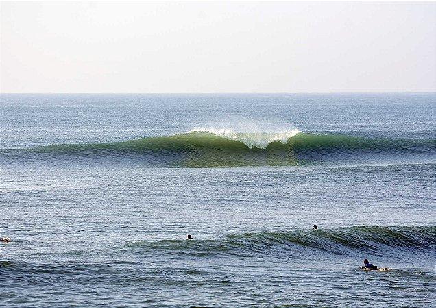 Onda quebrando ao fundo com surfistas
