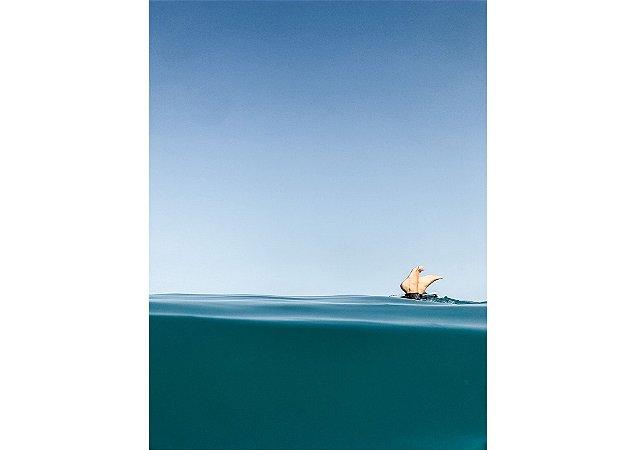 Barco velejando no horizonte com foco no mar