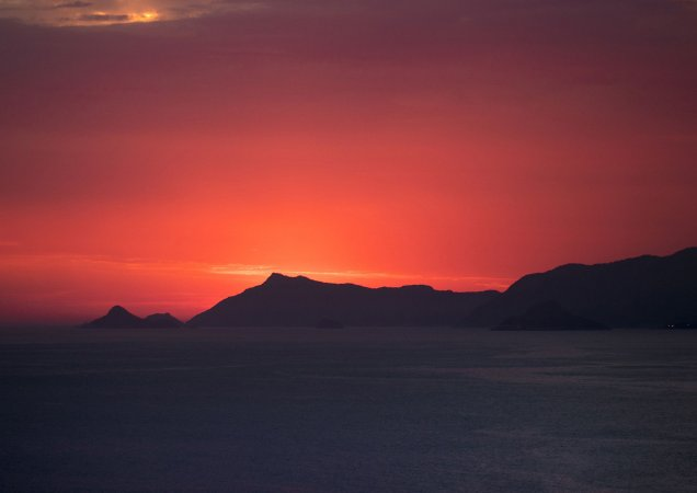 Pôr do sol avermelhado na praia da Barra da Tijuca, Rio de Janeiro