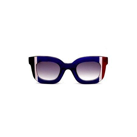 Óculos de Sol Gustavo Eyewear G31 10. Cor: Azul translúcido com listras preta e fumê e vermelho e fumê. Haste vermelhas. Lentes cinza.