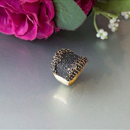 Anel dourado com cravação em zircônias e cristal ônix