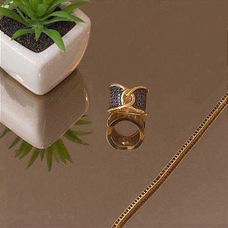 Anel dourado com detalhe entrelaçado cravejado com zircônias negras