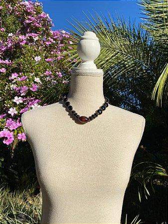 Colar curto com peças de polímero pretas e peça vermelha ao centro , e detalhes de metal banhado.