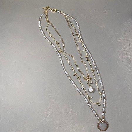 Conjunto de colares com cristais multicoloridos claros e correntes douradas.