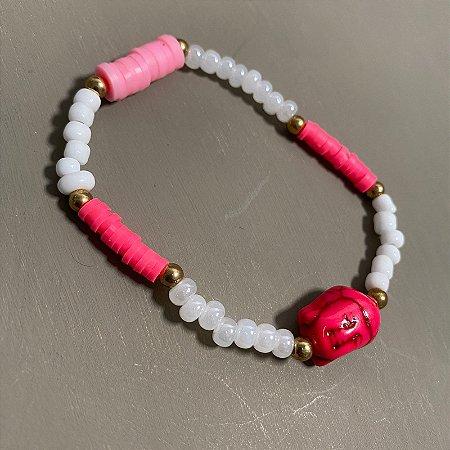 Pulseira de miçangas brancas, borrachinhas rosas e pingente indiano ao centro.