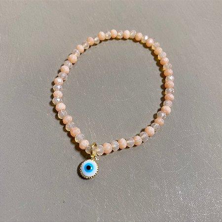 Pulseira de cristais lapidados nude e pingente de olho grego.