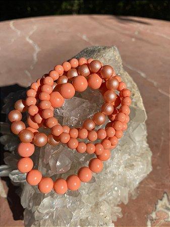 Conjunto de pulseiras esferas diversos tamanhos em tons coral e fosco.