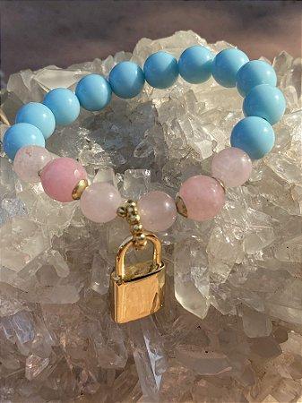 Pulseira de esferas em polímero azul claro e pedras quartzo rosa e pingente de metal banhado em formato de cadeado.