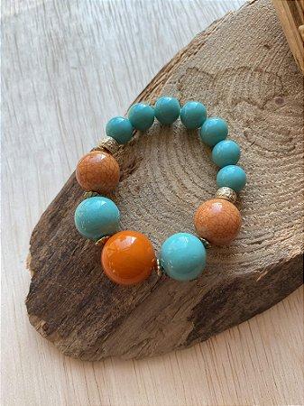Pulseira de esferas médias e grandes em polímero laranja e turquesa, com entremeios de metal banhado.