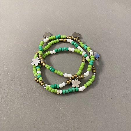 Conjunto de pulseiras de miçangas verdes e cru, entremeios e pingentes de metal banhado.