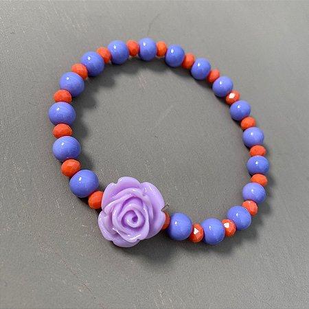 Pulseira de esferas em polímero lilás, cristais lapidados laranja e flor em polímero ao centro.