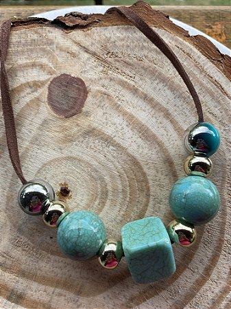 Colar curto com cordão marrom e peças em polímero turquesa.