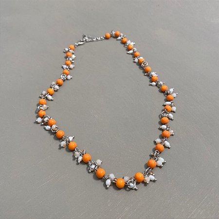 Colar curto alfinetado de vidro laranja e pingentes de pérolas barrocas e cristais tchecos lapidados.