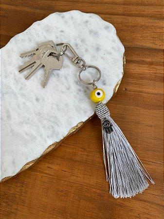 Chaveiro com pingente fio de seda cinza , esfera de olho grego e pingente de Hamsá.