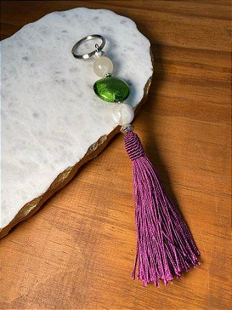 Chaveiro com pingente fio de seda lilás, esferas em polímero cru e vidro (tipo murano) verde musgo e entremeios de metal banhado.