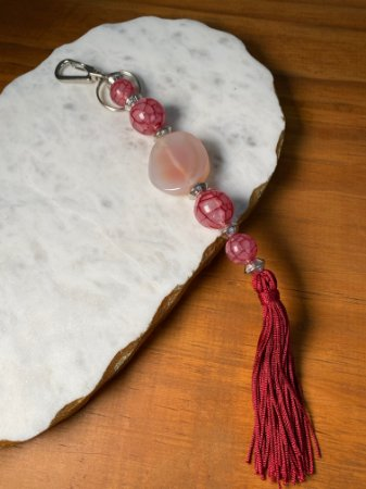Chaveiro com pingente fio de seda marsala, esferas em polímero rosado e entremeios de metal banhado.