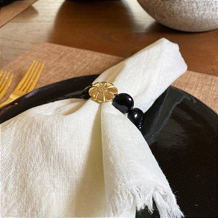 Kit com 4 porta guardanapos com peças em polímero preto e dourado ao centro.