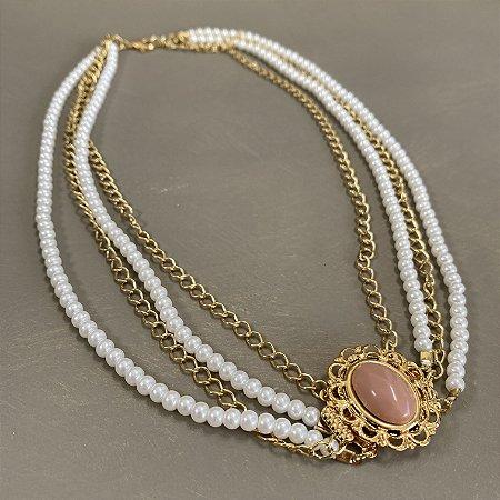 Colar curto camadas de pérolas e correntes em metal banhado dourado e pingente em polímero rosé ao centro.