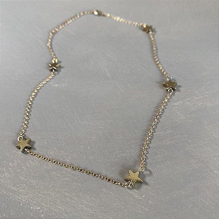 Colar gargantilha de corrente em metal banhado dourado e pingentes de estrelas.