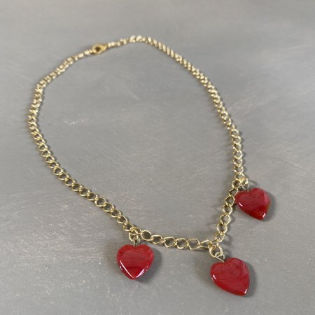 Colar gargantilha de corrente em metal banhado dourado e pingentes em polímero de coração.