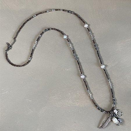 Colar longo com cristais tchecos lapidados fumê, entremeios de metal banhado, pérolas barrocas e penca com pingentes diversos.