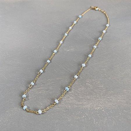 Colar gargantilha de corrente em metal banhado dourado, alfinetado com miçangas azul claro.