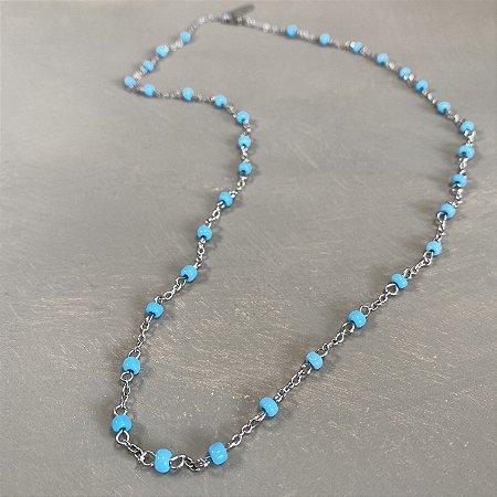 Colar curto de corrente em metal banhado níquel, alfinetado com miçangas azul.