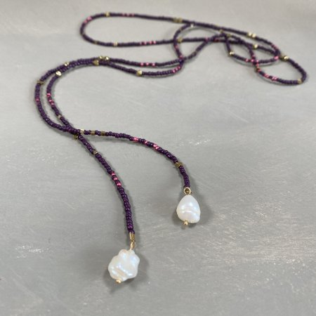Colar longo de amarrar com miçangas violetas e rosé, entremeios diversos de metal banhado e pingentes de pérolas barrocas.