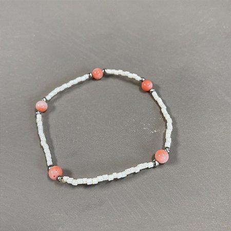 Pulseira de miçangas brancas peroladas, entremeios de metal banhado e esferas de pedra jaspe rosa.