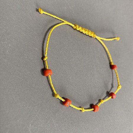 Pulseira com fecho regulável macramê fio amarelo e miçangas coral.