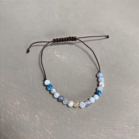 Pulseira com fecho regulável macramê fio marrom e esferas de vidro lapidado(tipo murano) azul claro.