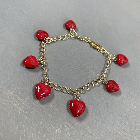 Pulseira  em metal banhado dourado e pingentes de coração em polímero.