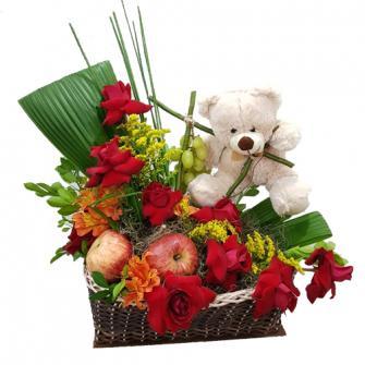 Arranjo vermelho com frutas e urso