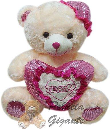 Urso gigante com coração e chapéu rosa.