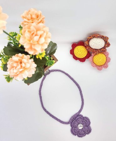 Cordão Zoe, na cor lilás, com uma flor e feito em crochê com linha de algodão