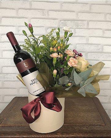 Cesta com vinho e arranjo floral