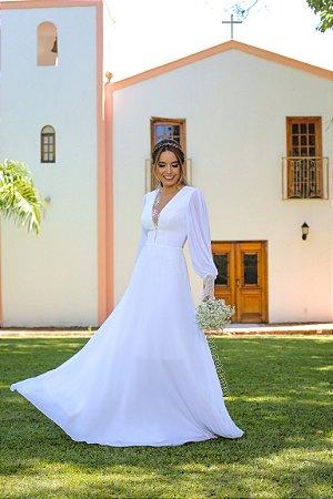 Vestido de noiva longo em crepe de seda, saia fluida detalhes em renda nos punhos e decote. Ideal para casamento religioso e no campo.