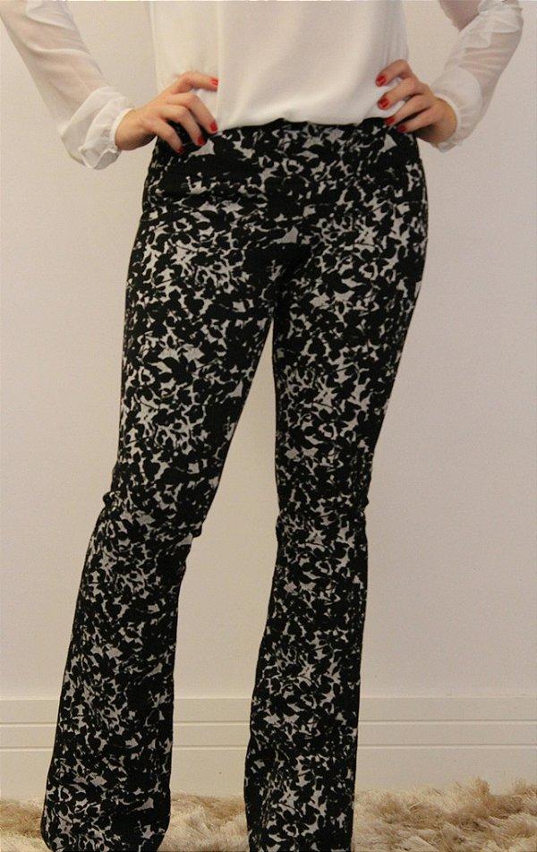 Calça feminina modelagem flare em tecido jacquard preto e branco com estampa de folhas